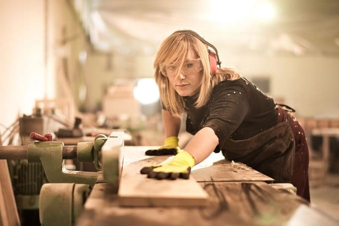 Woman Wearing Ear Protection While Woodworking