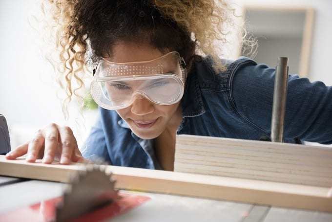 Young Woman Using Goggles While Woodworking