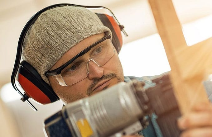 Man Wearing Earmuffs While Woodworking